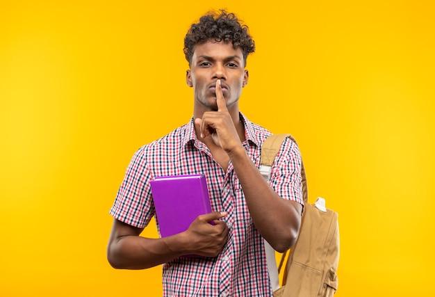 Fiducioso giovane studente afroamericano con zaino che tiene in mano un libro e fa un gesto di silenzio isolato sulla parete arancione con spazio di copia