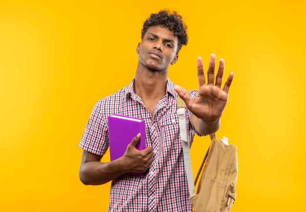 Confident young afro-american student with backpack holding book and gesturing stop hand sign isolated on orange wall with copy space