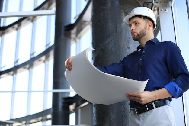 青写真を保持し、それを見ているネイビーシャツとヘルメットの自信を持って若い建築家。