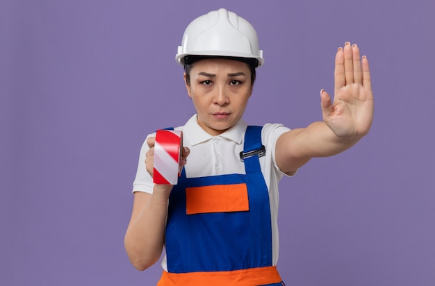 흰색 안전 헬멧을 들고 경고 테이프를 들고 정지 신호를 보내는 자신감 있는 젊은 아시아 건축업자 여성