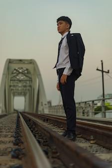 肩に掛かっているコートで鉄道の真ん中に立っている自信を持って若いアジア系のビジネスマン