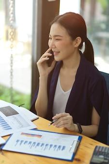 Уверенно молодые азиатские коммерсантки разговаривают на мобильном телефоне с деловыми партнерами