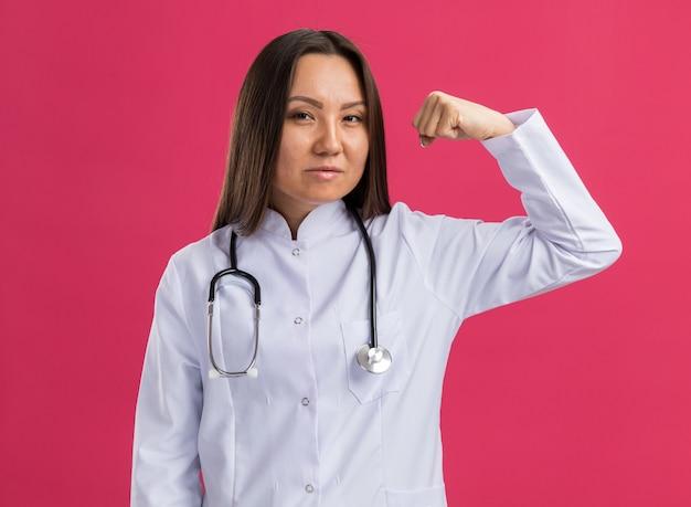 분홍색 벽에 격리된 강한 몸짓을 하는 정면을 바라보는 의료 가운과 청진기를 입은 자신감 있는 젊은 아시아 여성 의사