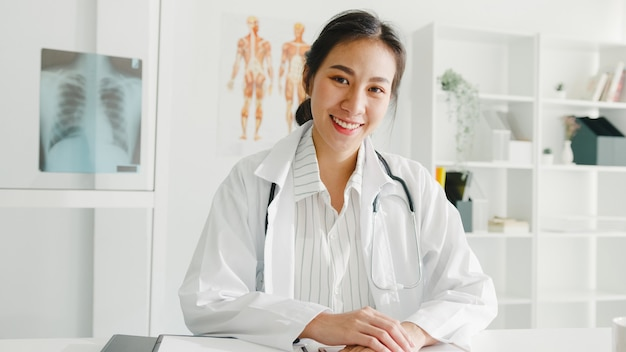 Confident young asian female doctor in white medical uniform with stethoscope