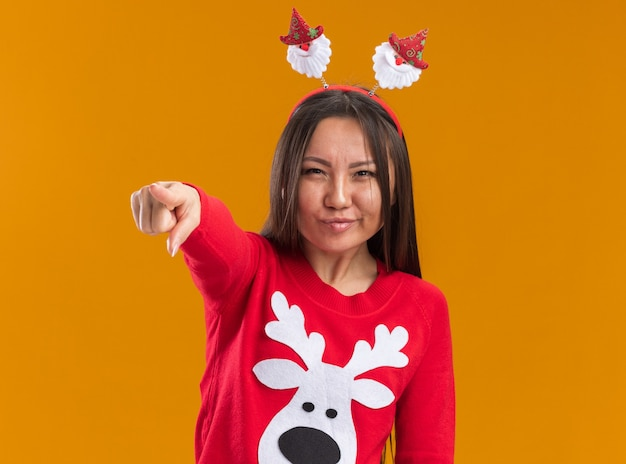 Confident young asian girl wearing christmas hair hoop with sweater showing you gesture isolated on orange background
