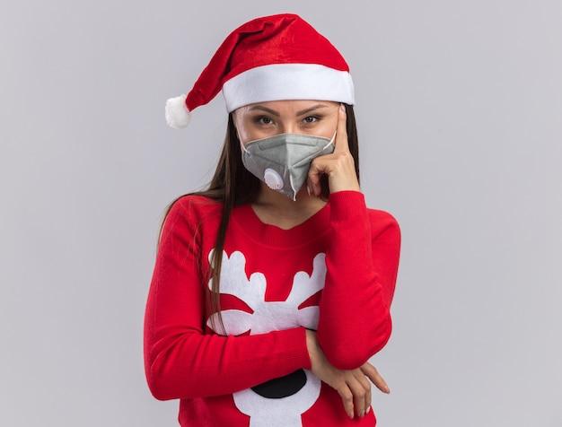 Fiduciosa giovane ragazza asiatica che indossa il cappello di natale con maglione e mascherina medica mettendo il dito sulla guancia isolato su sfondo bianco