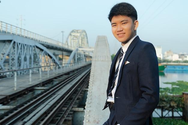 橋に寄りかかってスーツを着た自信を持って若いアジア人