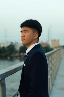離れている橋の上に立っているスーツで自信を持って若いアジア人