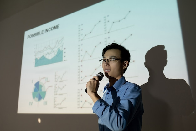 投資家に彼のビジネスアイデアを提示しながら、投影スクリーンに立ってマイクに向かって話す眼鏡の自信を持って若いアジア人