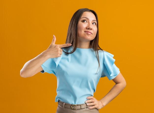 Fiduciosa giovane donna asiatica che guarda in alto indicando il lato isolato sulla parete arancione