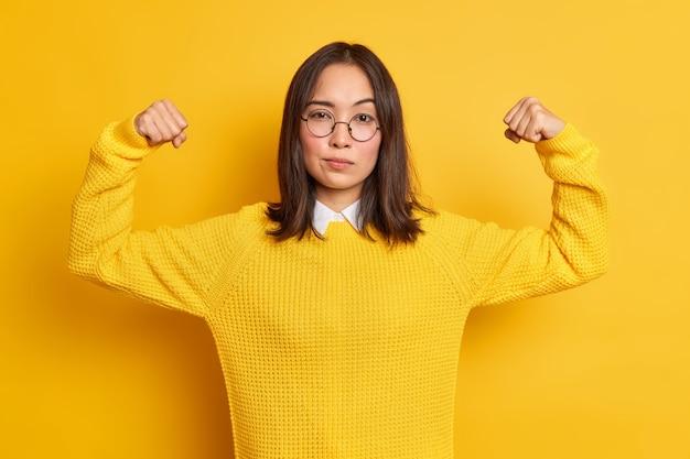 Fiduciosa giovane donna asiatica mostra i muscoli delle braccia si sente come l'eroe dimostra il suo potere e la forza sembra che indossa seriamente un maglione rotondo con occhiali da vista.