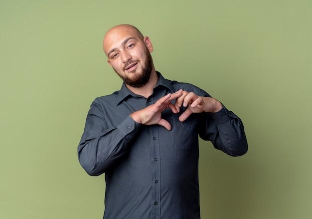 Uomo calvo giovane sicuro della call center che fa il segno del cuore isolato su verde oliva con lo spazio della copia
