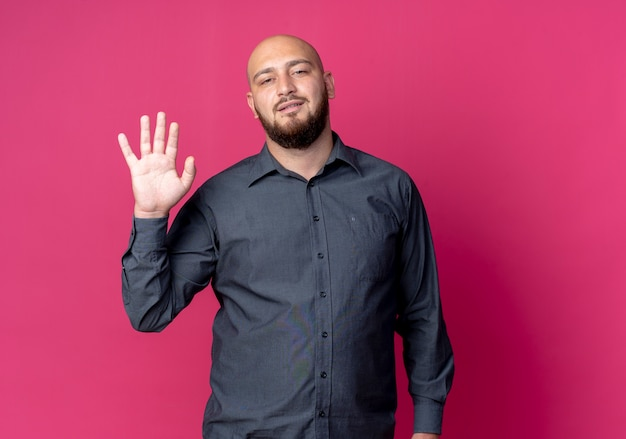 안녕 제스처를 하 고 자신감 젊은 대머리 콜 센터 남자 복사 공간이 진홍색에 고립