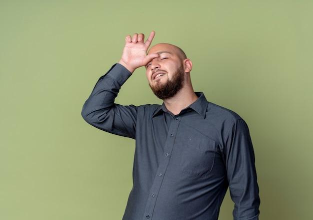 Уверенный молодой лысый человек из колл-центра делает жест неудачника на оливково-зеленом фоне с копией пространства