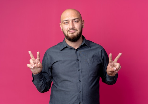 Confident young bald call center man doing peace signs isolated on crimson