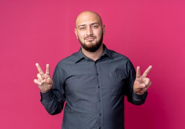 진홍색에 고립 된 평화 표지판을하고 자신감이 젊은 대머리 콜 센터 남자