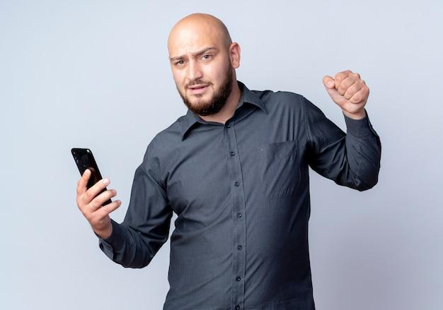 Uomo calvo giovane sicuro della call center che tiene il telefono cellulare e il pugno di serraggio isolato su bianco