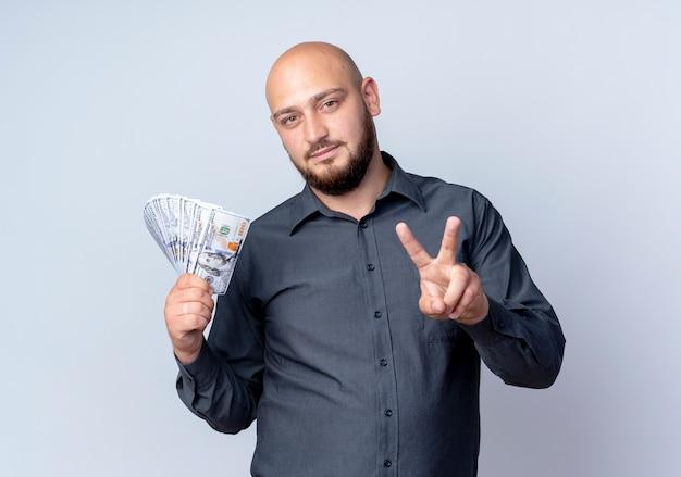 자신감이 젊은 대머리 콜 센터 남자 돈을 들고 흰색에 고립 된 평화 서명 하
