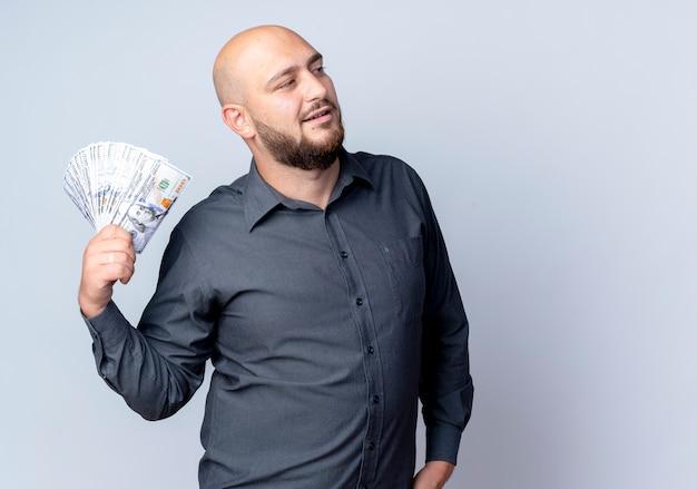 자신감이 젊은 대머리 콜 센터 남자 복사 공간 흰색 절연 측면을보고 돈을 들고