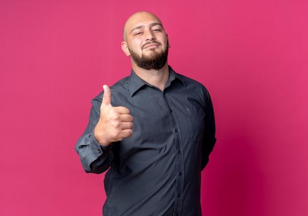 自信を持って若いハゲのコールセンターの男性が背中の後ろに手を保ち、コピースペースで深紅色に孤立して親指を表示