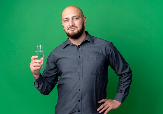 自信を持って若いハゲのコールセンターの男が腰に手を保ち、緑に隔離された水のガラスを保持します。