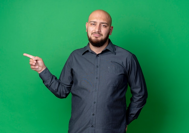 コピースペースで緑に隔離された側を指している自信を持って若いハゲのコールセンターの男