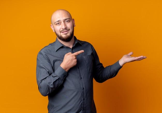 Uomo calvo giovane sicuro della call center che mostra la mano vuota e che indica esso isolato sull'arancio