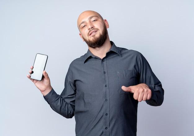 Uomo calvo giovane sicuro della call center che mostra il telefono cellulare e che indica esso isolato su bianco