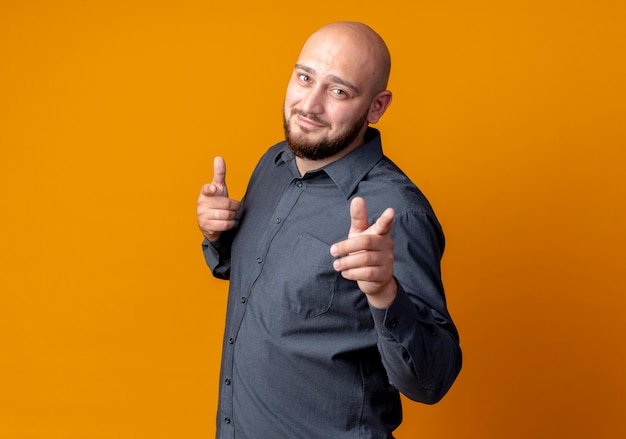 Confident young bald call center man standing in profile view doing you gesture isolated on orange  with copy space