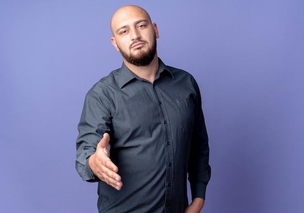自信を持って若いハゲのコールセンターの男がコピースペースで紫に分離された手を身振りで示す