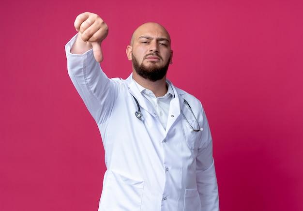 Fiducioso giovane medico maschio calvo che indossa veste medica e stetoscopio con il pollice verso il basso