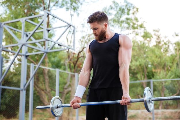 Уверенный молодой бородатый фитнес-мужчина делает упражнения со штангой на открытом воздухе