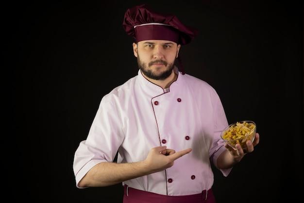 Уверенный молодой бородатый шеф-повар в униформе, указывая указательными пальцами на миску макарон в руке