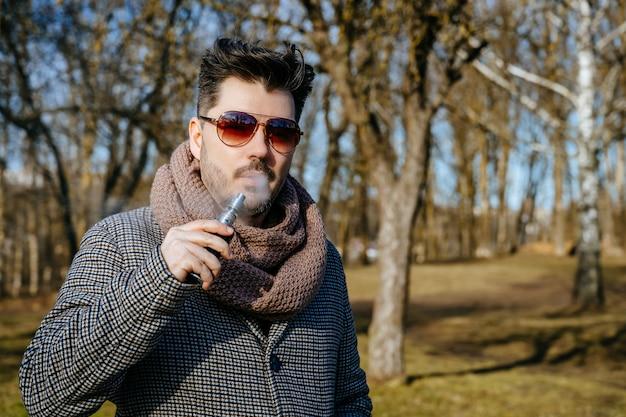 サングラスvape電子タバコで自信を持って若いひげを生やした男性。公園で屋外電子タバコを吸う若いハンサムなひげを生やした流行に敏感な男。閉じる。