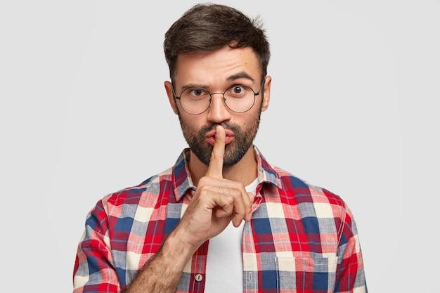 自信を持って若いひげを生やした男性は、shhジェスチャーを行い、人差し指を口に当て、眉を持ち上げ、沈黙を求め、集中できず、白い壁に隔離されます。人と静けさの概念