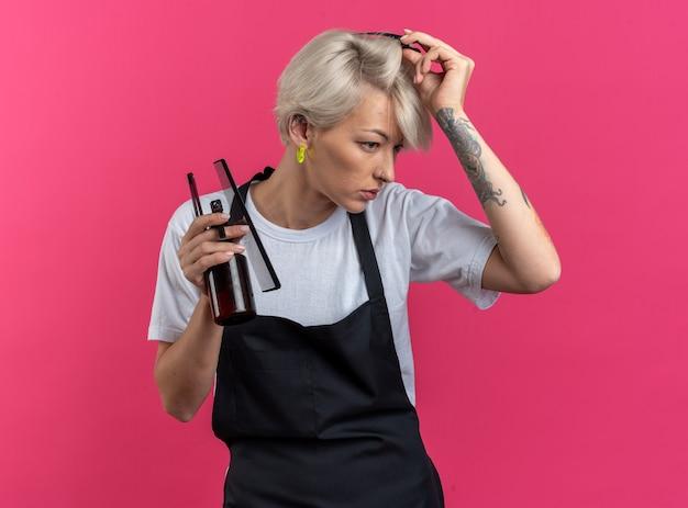 Уверенная молодая красивая женщина-парикмахер в униформе, держащая парикмахерские инструменты, надевая волосы на волосы, изолированные на розовой стене