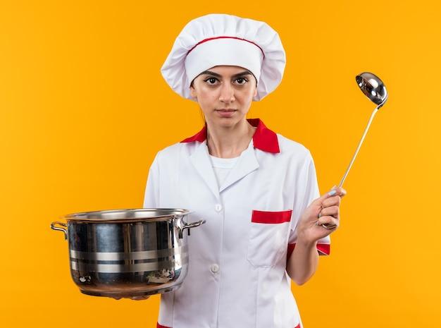 Fiduciosa giovane bella ragazza in uniforme da chef che tiene pentola con mestolo