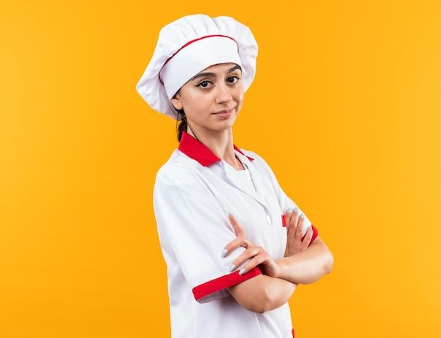 복사 공간이 있는 주황색 벽에 격리된 요리사 유니폼을 입은 자신감 있는 젊은 아름다운 소녀