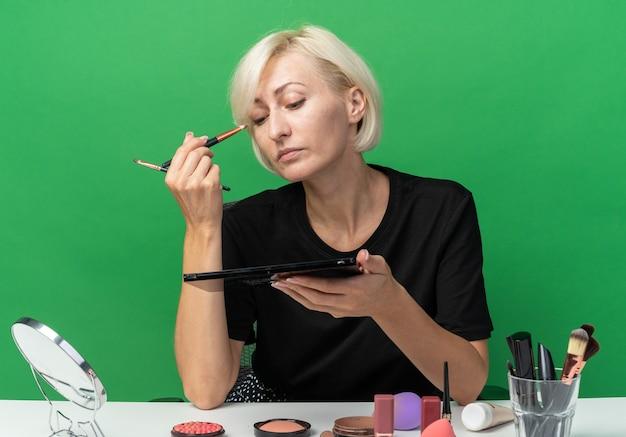 Уверенная молодая красивая девушка сидит за столом с инструментами для макияжа, применяя тени для век с кистью для макияжа, изолированной на зеленой стене