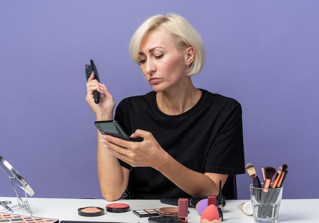 Уверенная молодая красивая девушка сидит за столом с инструментами для макияжа, держа расческу и глядя на телефон в руке, изолированной на синей стене