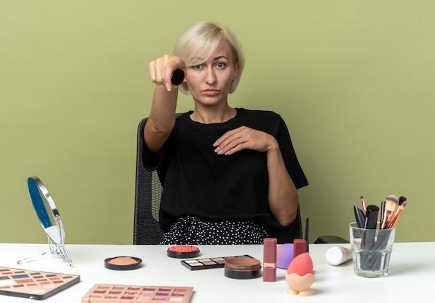 Уверенная молодая красивая девушка сидит за столом с инструментами для макияжа, протягивая кисть для пудры на камеру, изолированную на оливково-зеленой стене