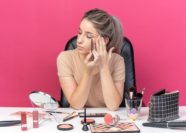 Confident young beautiful girl sits at table with makeup tools draw arrow with eyeliner isolated on pink wall