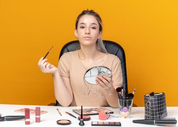 La giovane bella ragazza sicura si siede alla tavola con gli strumenti di trucco che tengono la spazzola di trucco con lo specchio isolato sulla parete arancione