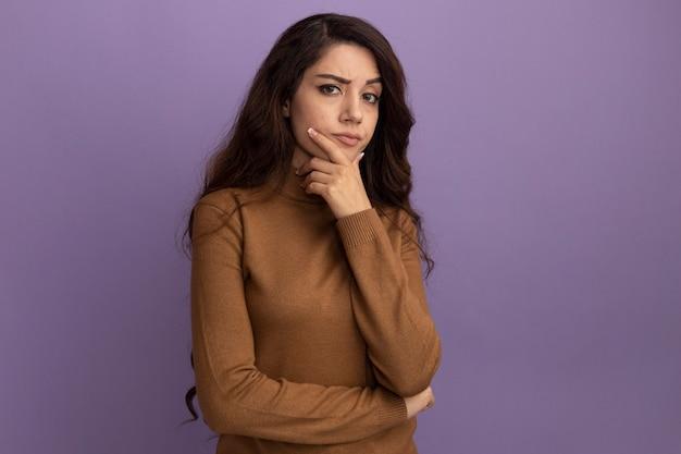 コピースペースと紫色の壁に分離されたあごに手を置く茶色のタートルネックのセーターを着ている自信を持って若い美しい少女