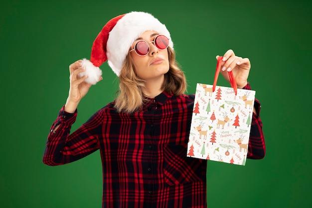 Уверенная молодая красивая девушка в новогодней шапке с очками, держащая подарочный пакет на зеленом фоне