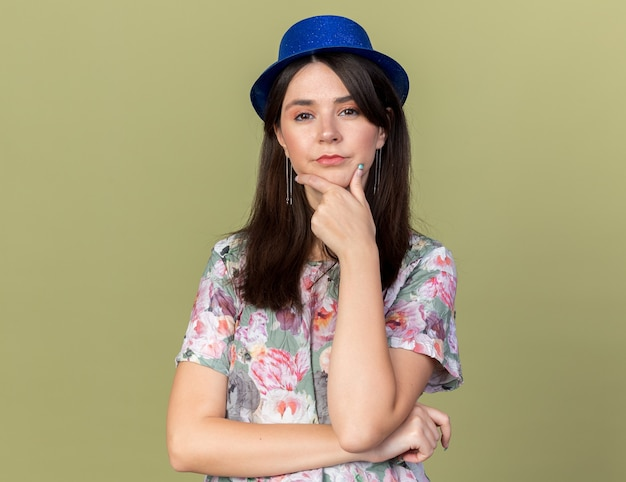 Confident young beautiful girl wearing party hat grabbed chin