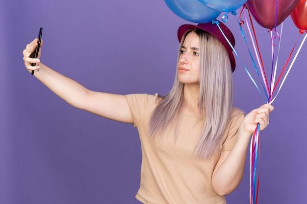 風船を持ってパーティーハットを身に着けている自信を持って若い美しい少女は自分撮りを取ります