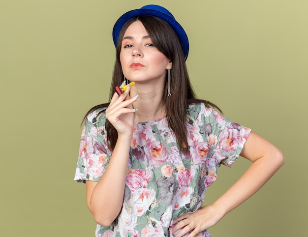 Confident young beautiful girl wearing party hat holding party whistle putting hand on hip