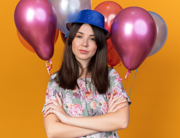 Confident young beautiful girl wearing party hat standing in front balloons crossing hands isolated on orange wall