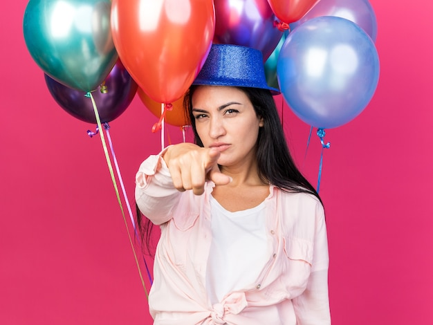 Confident young beautiful girl wearing party hat standing in front balloons showing you gesture isolated on pink wall